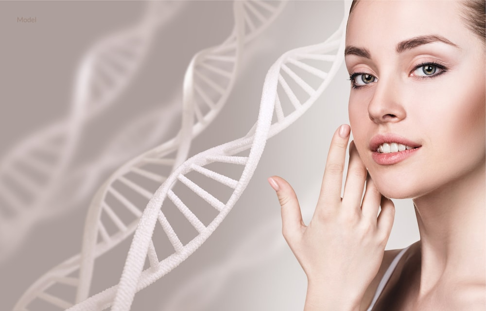 Woman caressing her face with DNA chains behind her. Stem cell concept.
