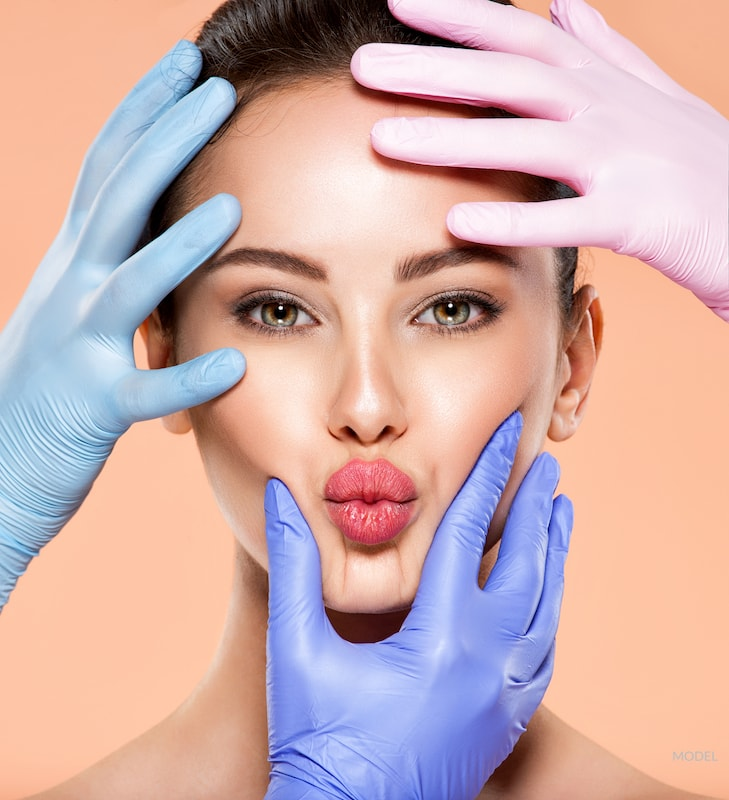 Woman puckering her lips with her face surrounded by doctor's hands.