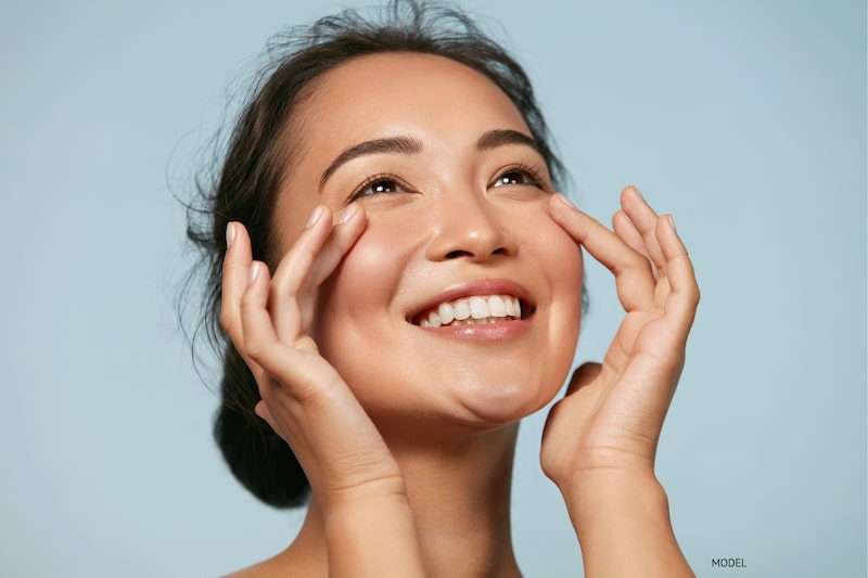 Young, Asian woman enjoying the effects of a youthful-looking face against a light blue backdrop.
