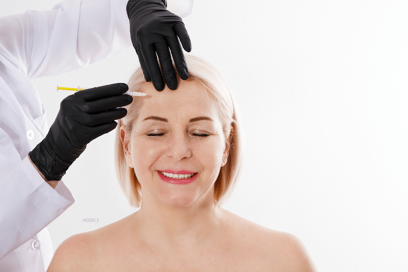 Woman getting a facial injection in forehead.